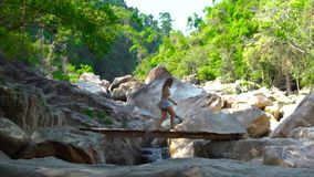 Beautiful woman walking on wooden bridge over rapid river in mountains. Woman tourist walking on bridge on background. Beautiful woman walking on wooden bridge stock video