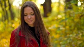 Beautiful girl walks in the autumn forest and enjoys good weather. Slow motion. Beautiful woman walks through the autumn forest and enjoys good weather. Weekend stock footage