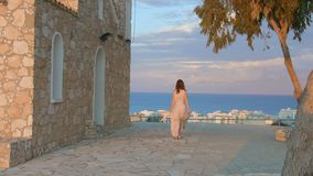 Beautiful woman walks on sidewalk, stops to enjoy amazing sea view. Resort town