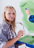 Beautiful woman during wall painting. Portrait of a beautiful young women during wall painting royalty free stock image
