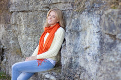 Beautiful woman in warm clothes sitting against stone wall Royalty Free Stock Photography