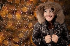 Beautiful woman with warm jacket under snowfall Stock Images