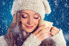 Beautiful woman in warm sweater. With snowflakes around her, on blue background Stock Images
