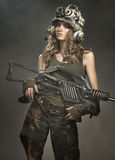 Beautiful woman warrior. In a helmet with a weapon Royalty Free Stock Photo