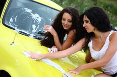 The beautiful woman washes the car Stock Photo