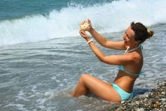 Beautiful woman washes seashell in sea Stock Images