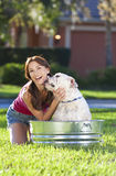Beautiful Woman Washing Her pet Dog In A Tub stock photos