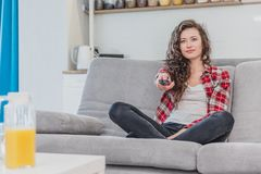 A beautiful woman watches the TV and is sitting on the couch and holds the remote control in his hand. A brunette in a royalty free stock photo