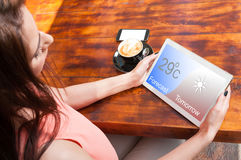 Beautiful woman watching forecast on her tablet. And drinking a fresh coffee royalty free stock photo