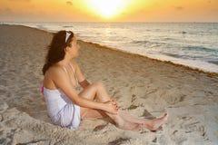 Beautiful woman watching sunrise. On the beach Stock Photo
