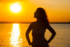 Beautiful woman watching the sunset while sitting near the water Stock Images