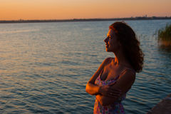 Beautiful woman watching the sunset while sitting near the water Stock Photography