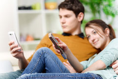 Beautiful woman watching tv while her lover is watching a screen Royalty Free Stock Images