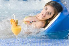 Beautiful woman in a water bed in spa center Stock Photos