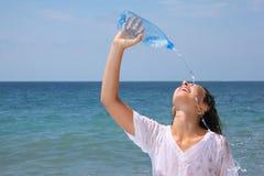 Beautiful woman watering from bottle on seacoast Stock Photo