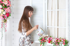Beautiful woman watering flowers on the windowsill. Spring royalty free stock photo