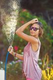 Beautiful woman watering roses with a garden hose. Summer garden, watering - beautiful woman watering roses with garden hose in blooming summer garden stock images
