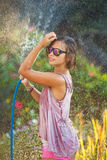 Beautiful woman watering roses with a garden hose. Summer garden, watering - beautiful woman watering roses with garden hose in blooming summer garden stock photos