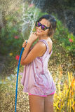 Beautiful woman watering roses with a garden hose Stock Photo