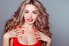 Beautiful woman with wavy hair and red manicure nails on grey ba Royalty Free Stock Photos