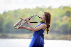 Beautiful woman wear blue evening dress sound saxophone over mou. Ntains and rivers background Stock Photos