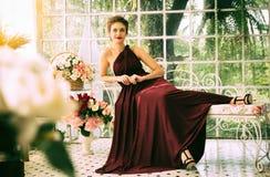 Beautiful woman lay down on the sofa. Beautiful woman wear red dress lay down on the sofa Stock Photos