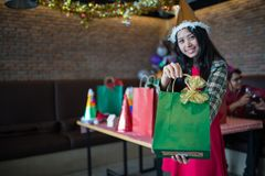 Beautiful woman wear red dress and santa claus hat showing green gift bag on hand at restaurant, Christmas party royalty free stock image