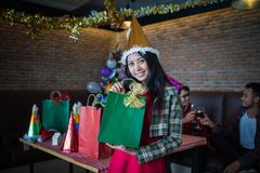 Beautiful woman wear red dress and santa claus hat showing green gift bag on hand in restaurant. concept of Christmas party royalty free stock photos