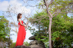 Beautiful woman wear red evening dress holding saxophone stand o. N the rocks Royalty Free Stock Image
