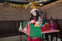 Woman wear santa claus hat showing green gift bag on hand in restaurant. concept of Christmas party and New year party royalty free stock image