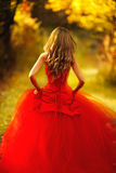 Beautiful woman wearing an amazing red gown. Girl in a red dress walking in the autumn forest Stock Image