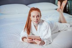 Beautiful woman wearing bathrobe and using digital tablet while relaxing on bed. Beautiful redhead woman wearing bathrobe and using digital tablet while lying on royalty free stock photos