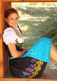 Beautiful Woman Wearing Bavarian Dirndl Dress. Beautiful red-head women wearing a traditional bavarian dirndl dress sitting in a window Stock Photo