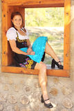 Beautiful Woman Wearing Bavarian Dirndl Dress. Beautiful red-head women wearing a traditional bavarian dirndl dress sitting in a window Royalty Free Stock Image