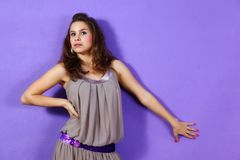 Beautiful woman wearing beige dress and lilac glit Royalty Free Stock Images