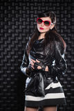 Beautiful woman wearing black leather jacket. And red sunglasses posing in the studio Stock Images
