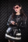 Beautiful woman wearing black leather jacket. And red sunglasses posing in the studio with a mobile phone Stock Photography