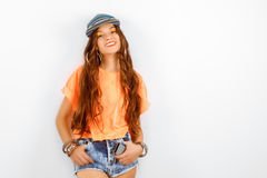 Beautiful woman wearing blue cap in orange T-shirt standing near white wall and smiling Royalty Free Stock Photography