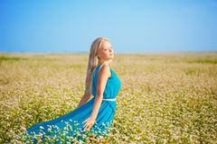 Beautiful woman wearing blue dress on a field Royalty Free Stock Photo