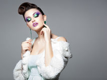 Beautiful woman wearing blue make-up and white fur posing in the studio. On grey background Royalty Free Stock Images
