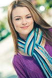 Beautiful woman wearing a blue scarf outdoors. Beautiful woman wearing a blue stripe scarf outdoors with a nice bokeh background Royalty Free Stock Images