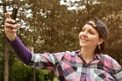 Beautiful woman wearing checked shirt and baseball cap taking selfie in the city park. Beautiful young woman wearing checked shirt and baseball cap taking royalty free stock photos