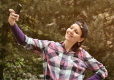 Beautiful woman wearing checked shirt and baseball cap taking selfie in the city park. Beautiful young woman wearing checked shirt and baseball cap taking royalty free stock image