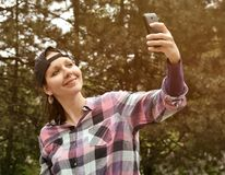 Beautiful woman wearing checked shirt and baseball cap taking selfie in the city park. Beautiful young woman wearing checked shirt and baseball cap taking stock photos