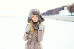 Beautiful woman wearing a coat and hat over snow in winter Stock Photography