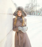 Beautiful woman wearing a coat jacket and hat over snow in winter Royalty Free Stock Photos