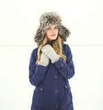 Beautiful woman wearing a coat jacket and hat over snow in winter Royalty Free Stock Image