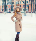 Beautiful woman wearing a coat jacket and hat over snow in winter. Park Stock Images