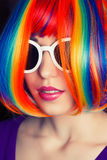 Beautiful woman wearing colorful wig and white sunglasses agains Stock Photo