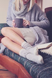 Beautiful Woman wearing  cozy sweater and Warm Wool Socks  reading a book sitting on comfortable sofa enjoying hot chocolate drink Royalty Free Stock Photos